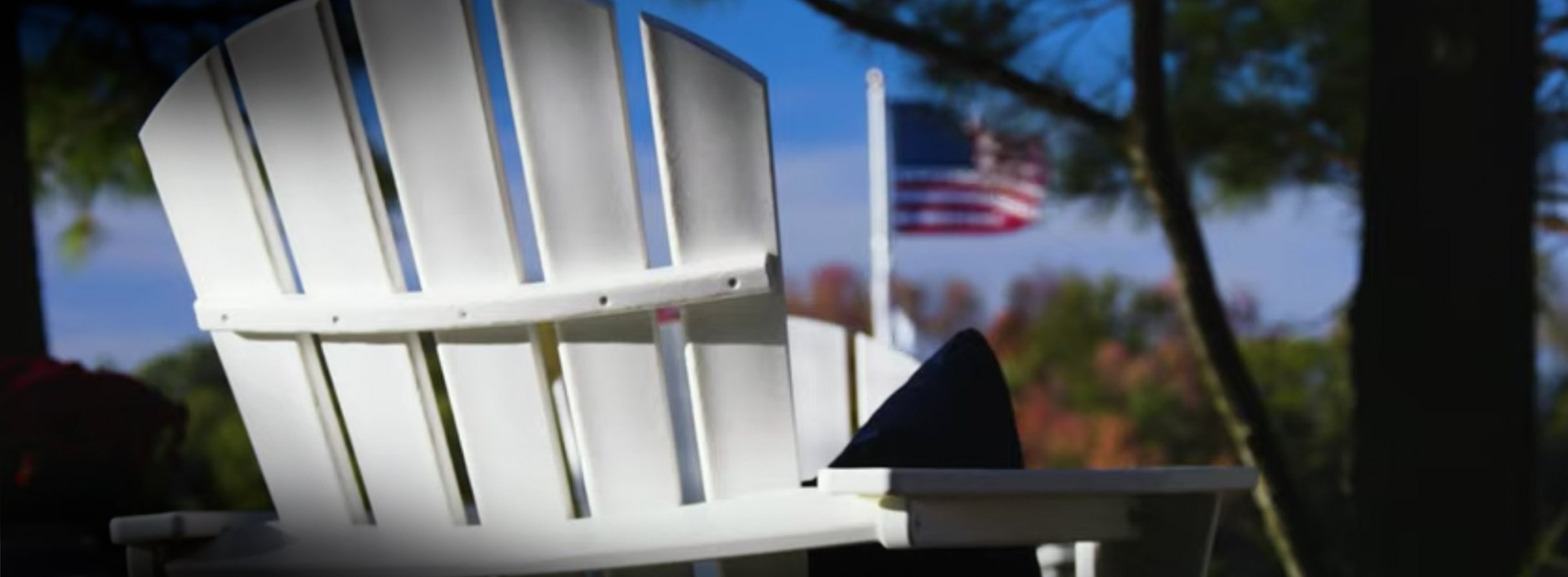 White POLYWOOD Adirondack Chair in front of American flag